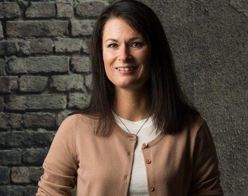 Linda Gunnarson, certified Swedish translator standing against dark background